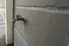 Gray old faucet on concrete wall royalty free stock images