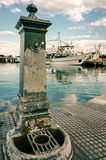 Old faucet in lagoon harbor with ships and green water backgrou Royalty Free Stock Image