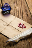 Old feather, envelope, sealing wax and ink bottle. On old wooden table Stock Photo