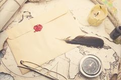Old feather, envelope, sealing wax. On the map stock image
