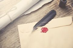 Old feather, envelope, sealing wax. On wooden table Stock Photos