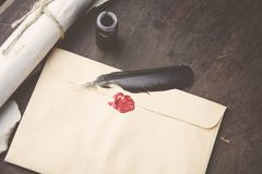 Old feather, envelope, sealing wax. On wooden table Stock Photography