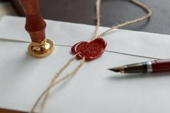 Old feather, envelope and sealing wax on wooden table stock photo