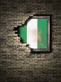 Old Federal Republic of Nigeria flag in brick wall. 3d rendering of a Federal Republic of Nigeria flag over a rusty metallic plate embedded on an old brick wall Stock Photography