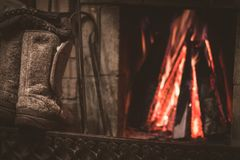 Old felt boots and fireplace with warm fire on the background. Winter in Russia royalty free stock photography