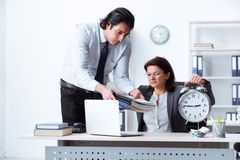 The old female boss and young male employee in the office royalty free stock photography