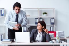 Old female boss and young male employee in the office. The old female boss and young male employee in the office stock photography