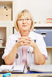 Old female doctor sitting at desk Royalty Free Stock Photos
