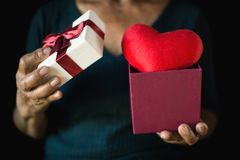 Old female hand holding gift box and red heart on black background. Concept valentine`s day ,selective and soft focus Stock Photo