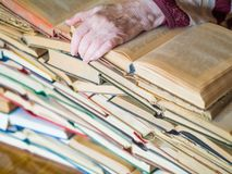 Old female hand is lying on stack of book. Elderly hand. Many hardback books. Education concept.  stock photos