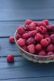 Old female hand puts in plate a handful of fresh ripe red raspbe. Big pile of fresh raspberries in the white bowl isolated on the white background Royalty Free Stock Photos
