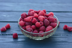 Old female hand puts in plate a handful of fresh ripe red raspbe. Big pile of fresh raspberries in the white bowl isolated on the white background Stock Image