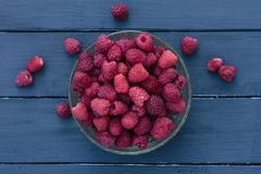 Old female hand puts in plate a handful of fresh ripe red raspbe. Big pile of fresh raspberries in the white bowl isolated on the white background Stock Photography