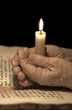 Old female hands with a candle. Religion concept Royalty Free Stock Photo
