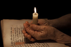 Old female hands with a candle Stock Image