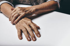 Old female hands on a table Stock Image