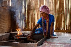 Old female karen hill tribe is cooking traditional in the cottage of northern Thailand at Mae Klang Luang. Mae Chaem, Chiang Mai Province royalty free stock photos