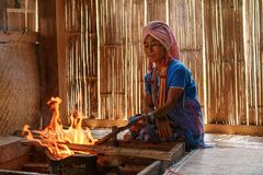 Old female karen hill tribe is cooking traditional in the cottage of northern Thailand at Mae Klang Luang. Mae Chaem, Chiang Mai Province royalty free stock photography