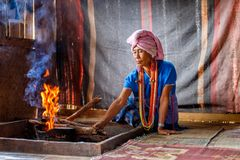 Old female karen hill tribe is cooking traditional in the cottage of northern Thailand at Mae Klang Luang. Mae Chaem, Chiang Mai Province stock photography