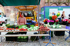 Old female market vendor under the Freiburg Cathedral, Germany royalty free stock photography