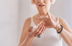 Old female sopping her finger into cream. Try it. Close up of retired woman that holding jar with cream in right hand keeping mouth opened while testing it stock photography