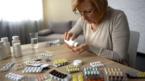 Old female taking capsules from bottle self-medication pills addiction obsession. Stock photo stock photos