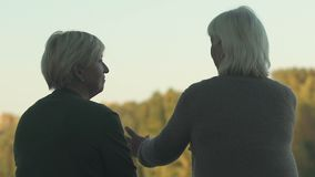 Old female talking to friend outside, resting in park together, communication. Stock footage stock video