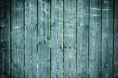 Old fence of boards with faded paint. Empty dark turquoise background, with vignette. Texture of wooden slats. Old fence of boards with faded paint. Empty dark royalty free stock images