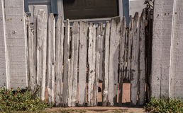 Old fence gate. Old picket concave closed  fence gate with peeled white paint Stock Photos