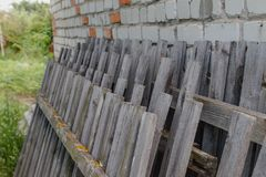 Old broken fence. The old fence has fallen off the brick wall Stock Photos