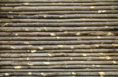 Old fence made from tree branches. Wall of twigs as background o stock photos