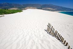 Old fence sticking out of deserted sandy beach dunes stock image