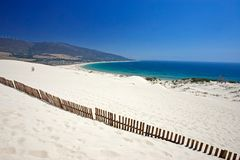 Old fence sticking out of deserted sandy beach dunes stock images