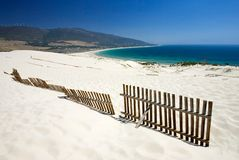 Old fence sticking out of deserted sandy beach dunes royalty free stock photo