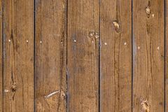 The of the old fence with vertical boards, light-brown faded color, knots on the pine boards stock photo