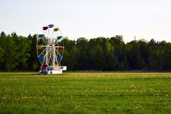 Traditional ferris wheel. Traditional white ferris wheel with multicoloured seats in a green grassy field Stock Photos