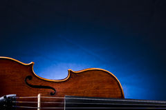 Old Fiddle Against A Blue Background Royalty Free Stock Photo