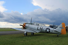 Old fighter american plane on green field side view Stock Photography