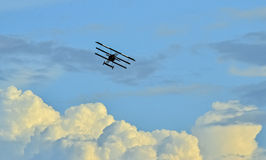 Old fighter plane flying on sky. Old antique fighter plane flying on cloudy sky Royalty Free Stock Photo