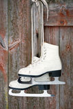 Old figure ice skates on a rustic wooden wall Royalty Free Stock Image