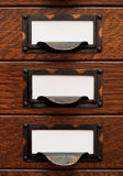 Old File Drawers With Blank Labels. Vertical stack of three small, old oak flat file drawers with white empty tags in tarnished brass label holders Royalty Free Stock Photo