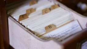 Old Files Alphabetically Searching. Person is searching for information handling an old wooden drawer with files database, sort by name, alphabetical stock video