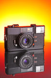 Old film camera. The background is a gradient from orange to yellow Stock Image