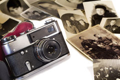 The old film camera and ancient photos on a white background. Stock Photography