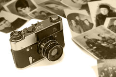 The old film camera and ancient photos on a white background. Stock Photo