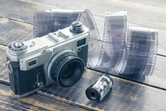 Old film camera, black and white film and film roll on a wooden Stock Image