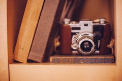 Old film camera in bookshelf royalty free stock photos