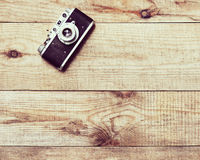 Old film camera on brown wooden background. Royalty Free Stock Photos