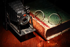 Old Film Camera. Closeup of old film camera near book on nice wooden background Stock Photo