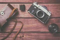 Old film camera with lens, case and film on wooden background. Vintage toned and top view Royalty Free Stock Photos